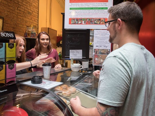 Sarah Caley, left and M'Kayla serves Sean Benvin one of the last coffee drinks at Brownstone Coffee House on Saturday.