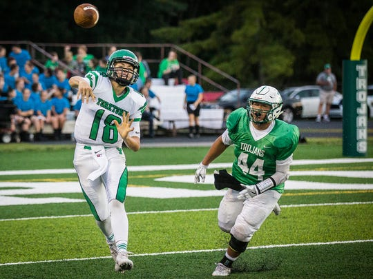 Yorktown's Brogan Miller passes while being pursued by New Castle's defense during their game at New Castle High School Friday, Sept. 16, 2016.