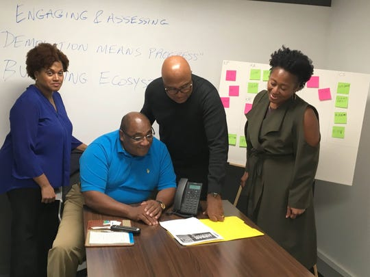 "L-R Karen A. Davis Burton, social media director, Reggie Barnett, vice-president, David Tarver, president, Regina Ann Campbell, TechTown Detroit Director of Place-Based Entrepreneurship (advisor). They are reviewing plans for the ""Give Us What You Got"" community improvement pitches campaign on Sept. 20, 2016 in Detroit. They are part of The Urban Entrepreneurship Initiative, a Mich.-based 501(c) (3) non-profit corporation established in 2015 and offering programming and resources that encourage, facilitate and enable the development of for-profit business solutions to address the needs of urban communities."