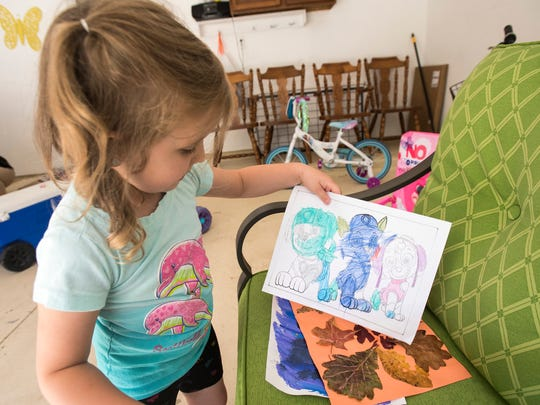 Olivia Marks, 4, shows off a drawing of characters from Paw Patrol that she colored at school Monday, June 11, 2018, in her home in Marysville. Olivia has an inoperable brain tumor, which she has been receiving medical care for.
