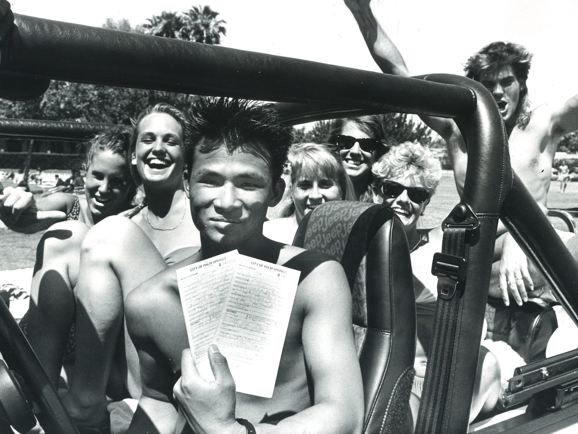 A spring breaker shows off a citation he received from