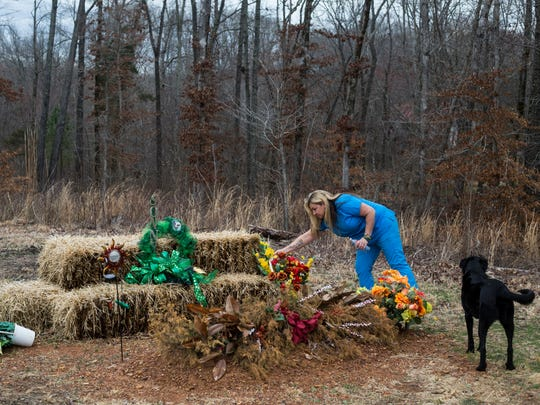 """Heather Melton adjusts a flower arrangement at the grave of her husband, Sonny, on the property that the couple had planned to move to Feb. 23, 2018. Melton moved into the home the couple were building two months after Sonny was killed in Las Vegas. """"We were just planning our future together and then it was just taken away."""""""