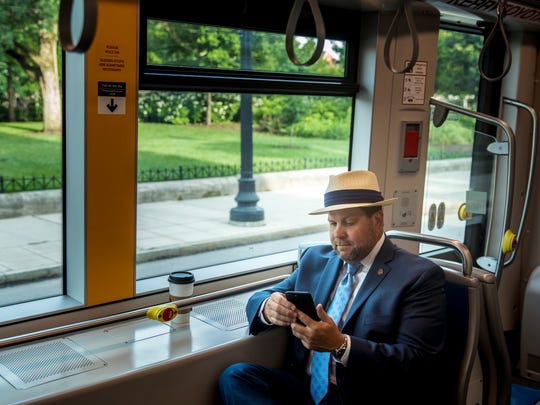 Jason Tyson, the general manager at Hilton Cincinnati Netherland Plaza, checks the morning news, while commuting to work on the Cincinnati Bell Connector Wednesday, June 18, 2018. Tyson moved to Cincinnati last fall and relies on the streetcar to travel around town.