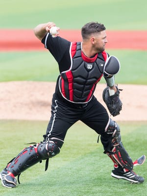 Louisville catcher Colby Fitch throws the ball to first during the college baseball game between the Louisville Cardinals and the Toledo Rockets at Jim Patterson Stadium.