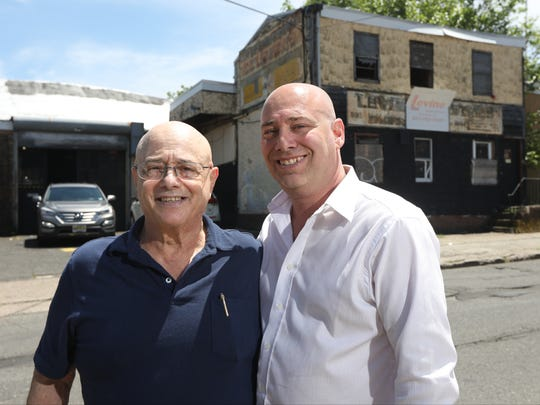 Ted and Jeffrey Levine pose for a photograph across