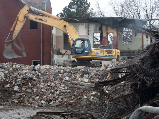 An excavator works at clearing away rubble Tuesday