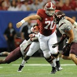 Alabama center Ryan Kelly blocks on a running play against Virginia Tech in August 2013. Kelly returns at center this season and must adjust to new starters on the offensive line.