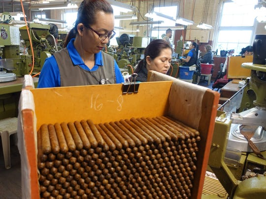 Workers at the at J.C. Newman cigar factory, using