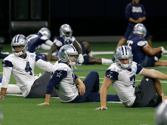 Cowboys quarterback Dak Prescott (4) stretches with backups Kellen Moore (17) and Cooper Rush (7) during practice in Frisco, Texas, Sept. 7, 2017.