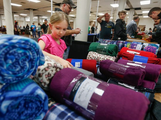 Zoe Diefenderfer, 8, arranges blankets on The Venues church table during the homeless count at the Shrine Mosque on Thursday, January 26, 2017. Zoe made a commercial on Facebook and collected more than 300 blankets to hand out to the homeless.