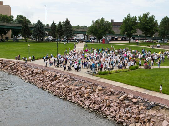 Protesters gather at Fawick Park in Sioux Falls, S.D. Saturday, June 30, 2018 for the Families Belong Together Rally.
