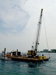 A barge holds in place an electrical generation device in the St. Clair River in 2010. The device uses technology patented through the University of Michigan.
