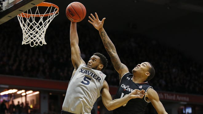 Xavier Musketeers guard Trevon Bluiett (5) dunks as Cincinnati Bearcats guard Troy Caupain (10) defends in the first half during the 84th annual Skyline Chili Crosstown Shootout basketball game between the Xavier Musketeers and the Cincinnati Bearcats, Thursday, Jan. 26, 2017, at Fifth Third Arena in Cincinnati.