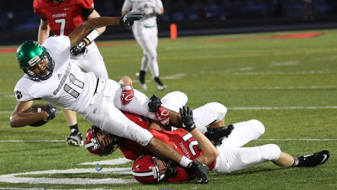 Greendale's Zach Harrison is brought down by Connor Vogt, bottom and Michael Friedel after a short gain. Coverage of the Pewaukee-Greendale football game Friday, September 16, 2016, at Pewaukee High School.