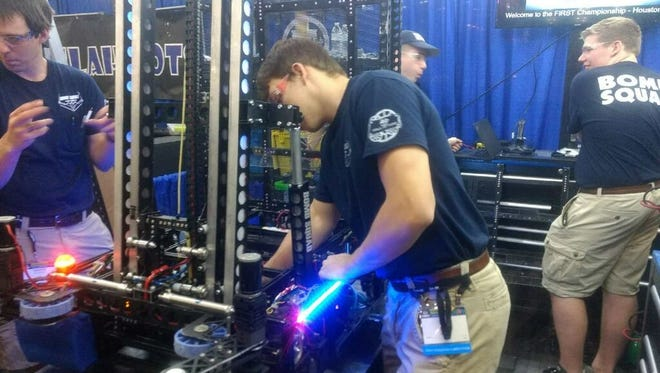 Members of the Mountain Home High School Bomb Squad robotics team work in the pits Friday during the FIRST World Championship in Houston, Texas.