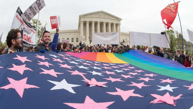 Protesters hold a pro-gay rights flag outside the US Supreme Court on April 25, 2015, countering the demonstrators who attended the March For Marriage in Washington, DC. The Supreme Court meets on April 28 to hear arguments whether same-sex couples have a constitutional right to wed in the United States, with a final decision expected in June.