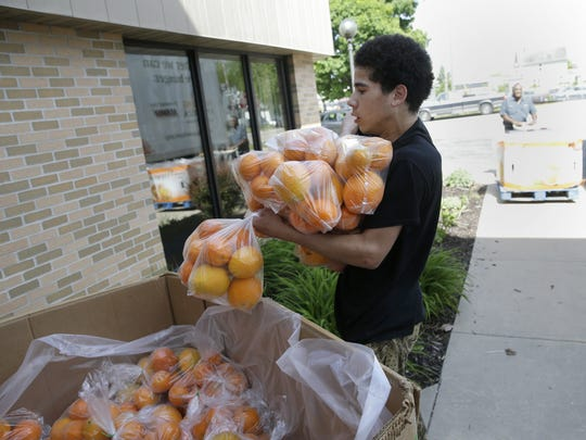 Gerald Lewis, a volunteer at Thursday's Summer Resource Fair at the Boys and Girls Club in Appleton, carries in bags of oranges.