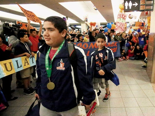Rudy Gutierrez—El Paso Times Henderson Middle School chess player Leo Gonzalez, foreground, arrives at the El Paso airport with his fellow team members amid cheers from parents and others Monday night at the El Paso Airport. The team, led by their coach, Saul Ramirez, captured first place in the U.S. Chess Federation National Junior High Chess Tournament in Louisville, KY Sunday.