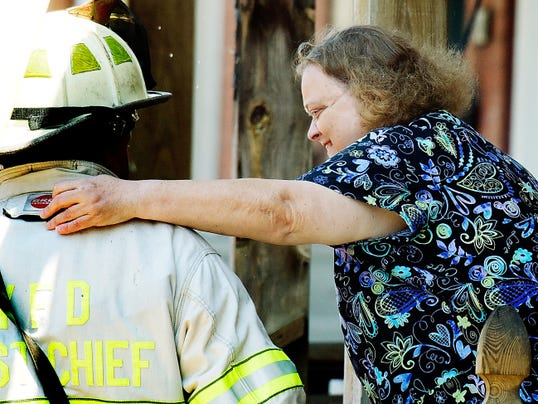 Peggy Clapper hugs York City Assistant Fire Chief Ed Hamilton after firefighters doused a blaze Thursday, July 16, 2015, at a row home next door to where Clapper and her sister live on Smyser Street.