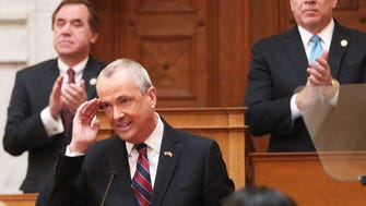 Assembly Speaker Craig Coughlin and Senate President Stephen Sweeney applaud Gov. Phil Murphy at the conclusion of his March budget address in the Assembly chambers.