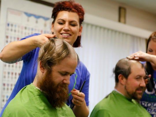 Hair stylist Rosemary Ihrcke shaves Buck Packer's hair