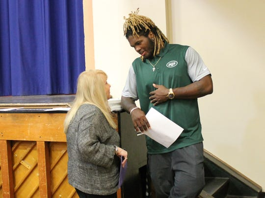 Linebacker Lorenzo Mauldin, right, speaks with the founder of STOMP out Bullying, Ross Ellis, shortly before a presentation at Belleville Middle School on Friday, May 19, 2017.