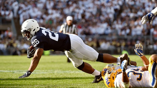 Penn State's Saquon Barkley is stopped by Pittsburgh's Bricen Garner and Saleem Brightwell in the second half of an NCAA Division I college football game Saturday, Sept. 9, 2017, at Beaver Stadium. Penn State defeated Pitt 33-14.