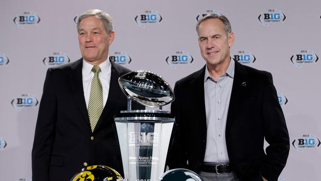 Iowa head coach Kirk Ferentz, left, and Michigan State head coach Mark Dantonio pose with the championship trophy during a news conference for the Big Ten Conference championship NCAA college football game Friday, Dec. 4, 2015, in Indianapolis.