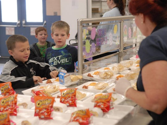 Fernley Elementary School students choose their entree Friday as kitchen manager Glenda Johnson, right, happily greets them.