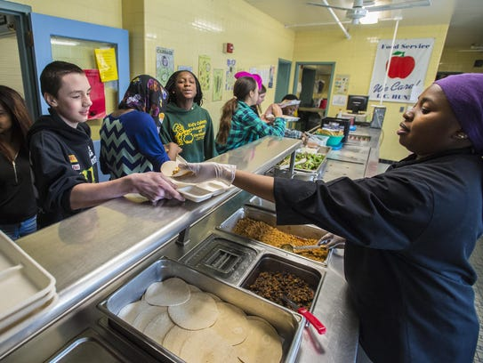 Ismahan Somo (right) serves tacos, part of an after-school