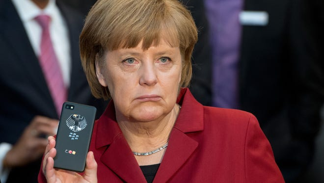 German Chancellor Angela Merkel presents a tap-proof mobile phone in March.