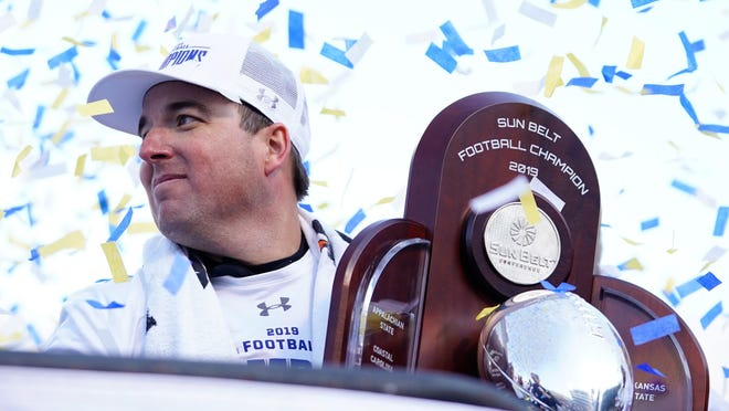 Appalachian State head football coach Eliah Drinkwitz holds the championship trophy after defeating Louisiana-Lafayette on Dec. 7 to win the Sun Belt Conference. Drinkwitz agreed to become the next head coach at Missouri later that day.