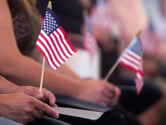 New U.S. citizens hold American flags during a 2006 naturalization ceremony in Mount Holly.