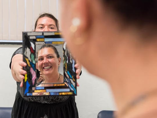 Chantal Matthews of Factory Designs holds a mirror for Christina Fabris of Wilmington as she admires a piece of jewelry at an Art in the Urban Garden event at Connections in Wilmington on Saturday.