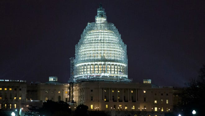 Lights illuminate the the U.S. Capitol, which is covered in scaffolding for ongoing restoration of the dome, on Jan. 14, 2015.