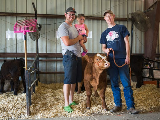 Scott Ruebush, left, poses with his daughter, Hayden Ruebush, 2, his brother Erik Ruebush, and one of their steers at the Augusta County Fair on Tuesday, August 4, 2015.