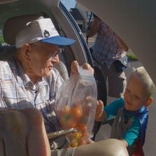 3-year-old Emmett Rychner eagerly grabs his bag of tomatoes from best friend, 89-year-old Erling Kindem.