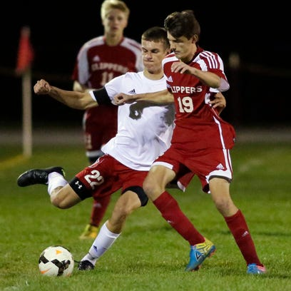 New Holstein's Jacob Conrad (22) prepares to kick the ball by Sturgeon Bay's Alec Fischer (19) Tuesday October 6, 2015 at New Holstein.