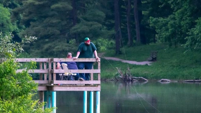 Two gentlemen fish off the dock at Memorial Park Lake in Barnesville recently.