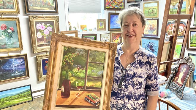 Eliane Ambrose is pictured here with a painting that she did, titled 'Waiting for My Master,' at her Greencastle home studio. JOHN IRWIN/ THE RECORD HERALD