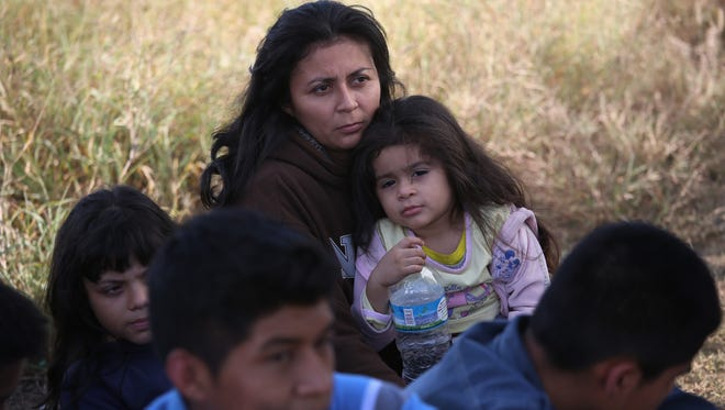 A Honduran mother holds her daughter, 3, after she turned her family in to Border Patrol agents after crossing the U.S.-Mexico border on Dec. 8, 2015, near Rio Grande City, Texas. She said she brought her two daughters to escape violence in the Central American country.
