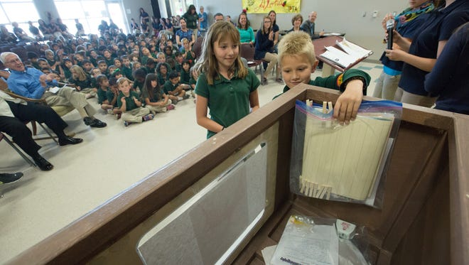 J. Paul Taylor Academy students Myles Jones, 8, and Scarlett Ellvinger, 8, place a classroom behavior clip chart and a class newsletter on Tuesday, May 24, 2016 into a time capsule marking the opening of the school's new building this academic year. The capsule will be opened in 15 years. Some of the other items placed in the capsule were autobiographies, year books, school uniforms and a video interview with J. Paul Taylor.