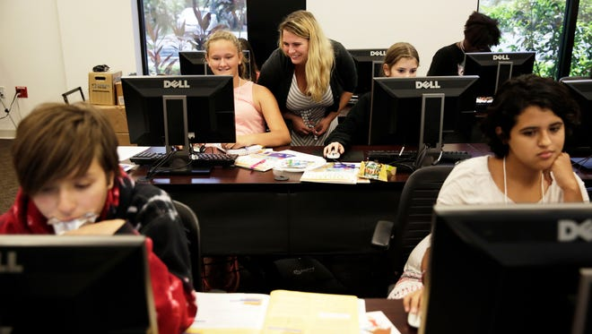 Program leader Alexa Brandstetter, 20, helps seventh-grader Eveline Murray at her computer during AspireIT Programming Technology Summer Camp at Hodges University in Naples on Friday, July 22, 2016. The camp is hosted by Hodges University's Fisher School of Technology and is for girls in grades six to 12.