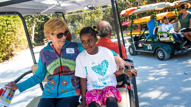 Sheila Wilbur, left, accompanies second-grader Lithiana Registre on a golf cart ride during Guadalupe Center's Buddy Day at Hideaway Beach on Marco Island on Monday, March 20, 2017. A group of students from the Guadalupe Center's after-school program were paired with volunteer big buddies for a day of activities at the beach.