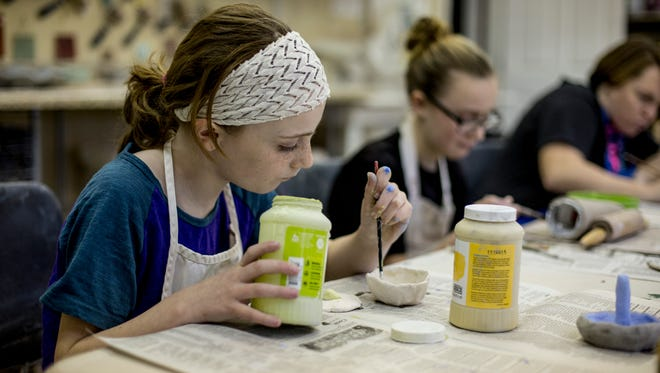"""Sydney Crull, of Marysville, paints glaze onto a piece during a """"Mudslinging"""" class at Studio 1219. People can get hands-on with art during a free event May 27 at Studio 1219."""