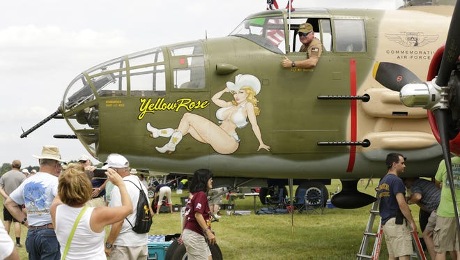 Tim Mullis, Gastonia, North Carolina has his photo taken by his sister Nancy Wrenn of Stanley, North Carolina in the Yellow Rose.  The B-25's were popular along the Warbird flight line display, at EAA in Oshkosh. Sixteen B-25 were involved in the raid over Tokyo known at Doolittle Raiders.