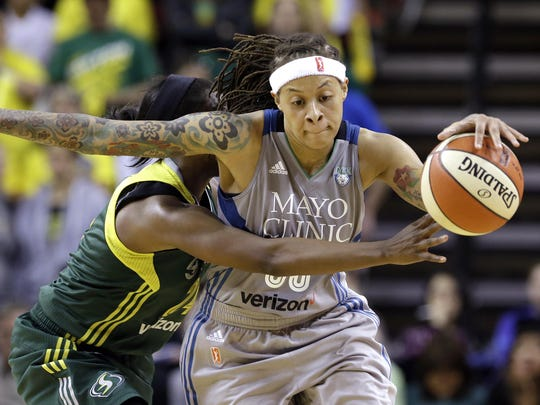 The Seattle Storm's Jewell Loyd, left, fouls Minnesota Lynx's Seimone Augustus late in the second half of a WNBA game on May 22 in Seattle.