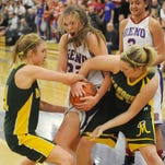 Reno's Morgan McGwire of Reno, center, fights for a jump ball against Manogue's Brianna Holt, left, and Madison Lewis during Reno's 56-47 win in the Division I North girls championship Saturday.