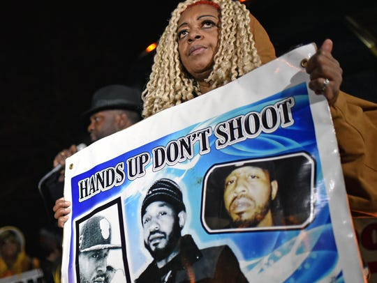 Sheila Reid, mother of Jerame Reid, hold up a poster