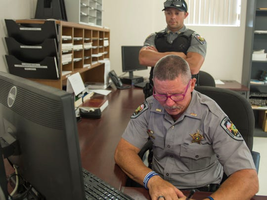 Lt. Steve Adams of the Autauga County Sheriff's Department explains the paperwork procedure to deputy Hunter Estes following a domestic call Thursday, June 21, 2018 during near Prattville, Ala.